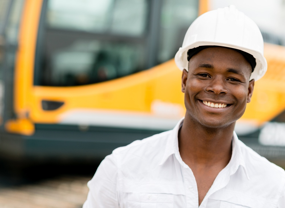 Construction worker with machines at the background looking happy .jpeg