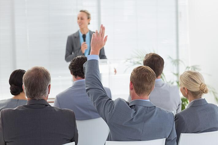 Pretty businesswoman talking in microphone during conference in meeting room.jpeg