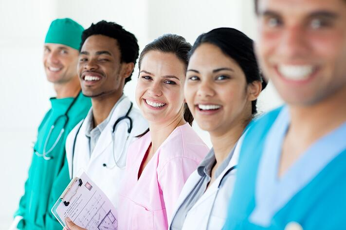 Smiling medical team in a line isolated on a white background.jpeg