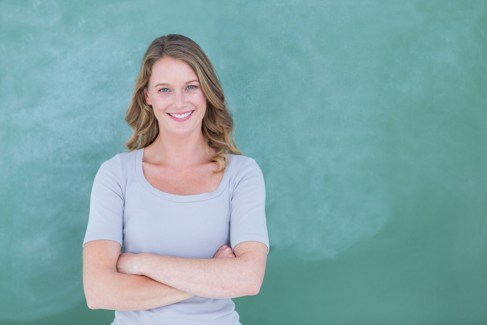 Smiling teacher standing in front of blackboard in classroom