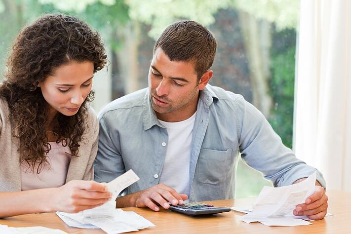 Young couple calculating their domestic bills at home.jpeg