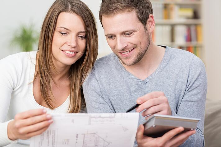 Young couple planning a new purchase sitting together pointing to a document held by the wife as the husband does the necessary calculations on a calculator.jpeg